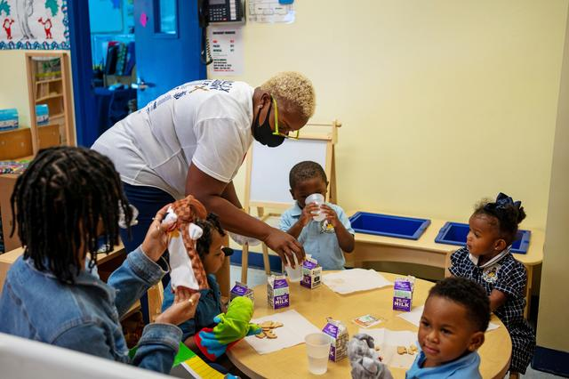 FILE PHOTO: Rochelle Wilcox delivers cartons of milk to the two-year-olds' classroom, as teacher Steneisha Morehead sits at left, with student Andrew Robair III, Amore Smalls, Roemello Jones, and King Adams, at Wilcox's Academy of Early Learning in New Orleans, Louisiana, U.S., August 24, 2021. Picture taken August 24, 2021.  REUTERS/Kathleen Flynn/File Photo