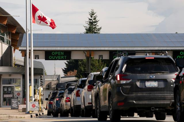 FILE PHOTO: People cross the U.S.-Canadian border after Canada opened the border to vaccinated Americans in Blaine, Washington, U.S., August 9, 2021.  REUTERS/David Ryder
